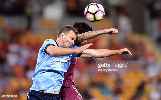 Jamie Maclaren of the Roar and Alexander Wilkinson of Sydney challenge for the ball during the round seven ALeague match between the Brisbane Roar...
