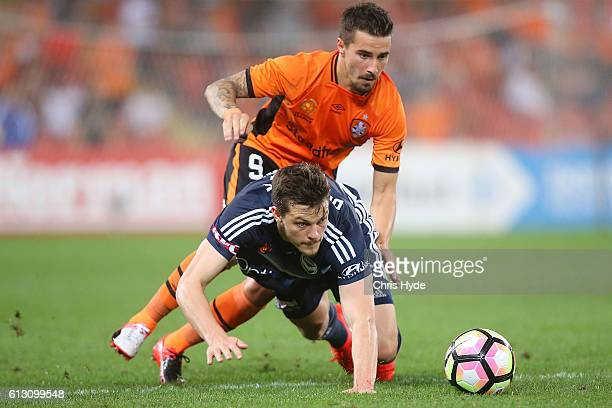 Jamie Maclaren of the Roar and James Donachie of the Victory compete for the ball during the round one ALeague match between the Brisbane Roar and...