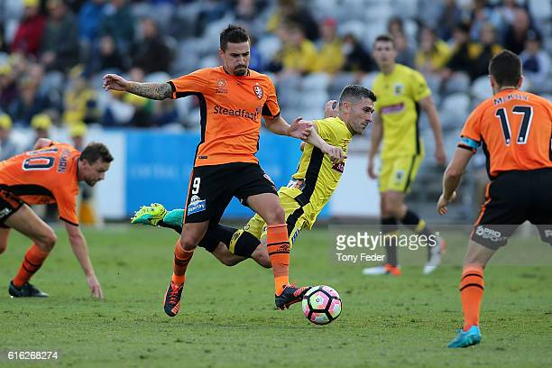 Jamie Maclaren of the Roar contests the ball with Nick Montgomery of the Mariners during the round three ALeague match between the Central Coast...