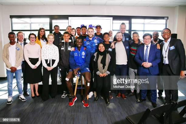 Jamie Macmillan and Majak Daw of the Kangaroos pose with community members during a North Melbourne Kangaroos AFL media opportunity at Arden Street...