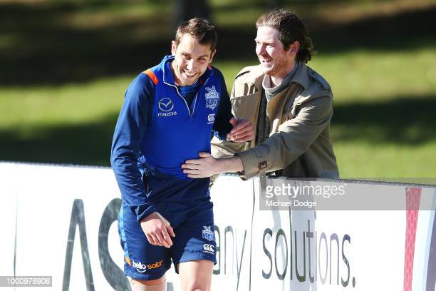 Jamie Macmillan of the Kangaroos catches up with a friend during a North Melbourne Kangaroos AFL training session at Arden Street Ground on July 18...