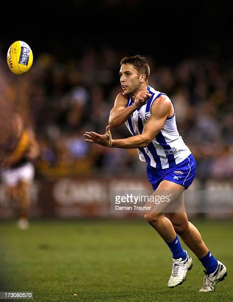 Jamie Macmillan of the Kangaroos handballs during the round 15 AFL match between the North Melbourne Kangaroos and the Richmond Tigers at Etihad...