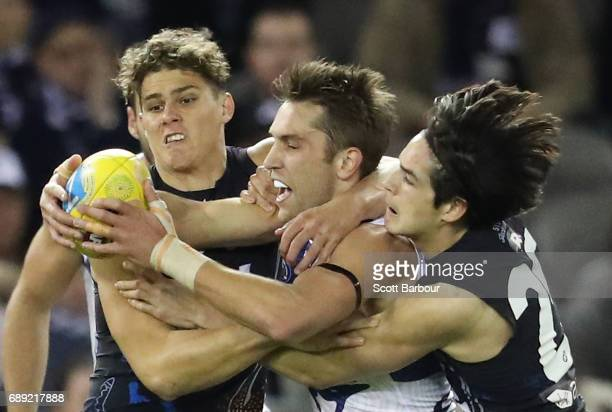 Jamie Macmillan of the Kangaroos is tackled by Charlie Curnow of the Blues during the round 10 AFL match between the Carlton Blues and the North...