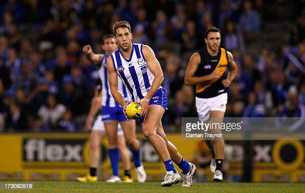Jamie Macmillan of the Kangaroos runs with the ball during the round 15 AFL match between the North Melbourne Kangaroos and the Richmond Tigers at...
