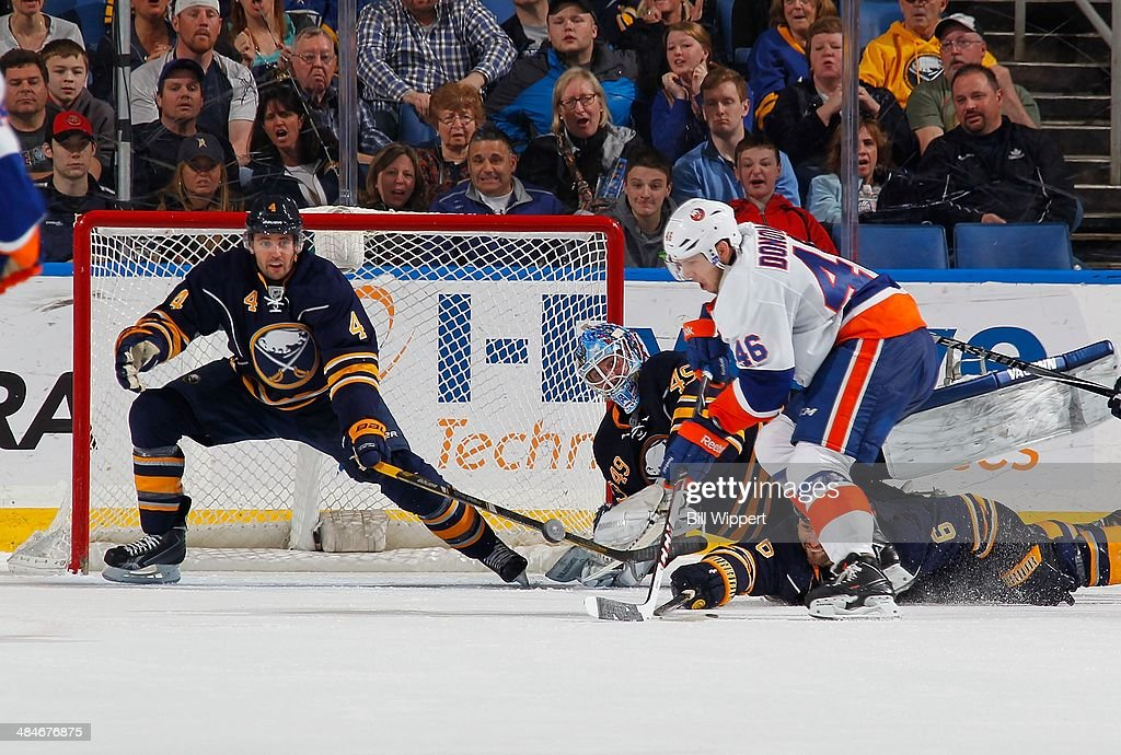 Jamie McBain #4, Mike Weber #6 and Connor Knapp #49 of the Buffalo Sabres combine to block the shot of Matt Donovan #46 of the New York Islanders on April 13, 2014 at the First Niagara Center in Buffalo, New York. New York won, 4-3.