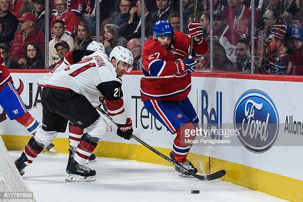 Jamie McBain of the Arizona Coyotes and Alex Galchenyuk of the Montreal Canadiens skate for the puck during the NHL game at the Bell Centre on...