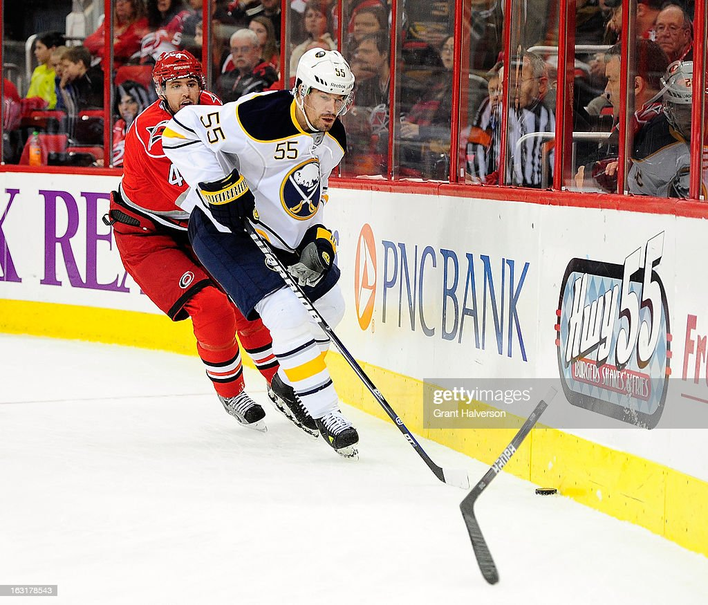 Jamie McBain #4 of the Carolina Hurricanes breaks his stick as he defends Jochen Hecht #55 of the Buffalo Sabres during play at PNC Arena on March 5, 2013 in Raleigh, North Carolina.