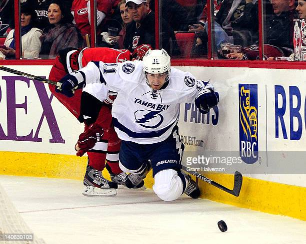 Jamie McBain of the Carolina Hurricanes knocks Tom Pyatt of the Tampa Bay Lightning off the puck during play at the RBC Center on March 3 2012 in...