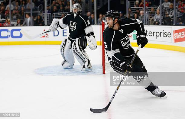 Jamie McBain of the Los Angeles Kings skates with the puck as Jonathan Quick of the Los Angeles Kings tends net during a game against the Chicago...