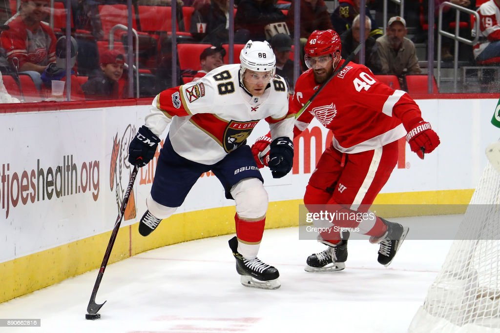 Jamie McGinn #88 of the Florida Panthers battles for the puck with Henrik Zetterberg #40 of the Detroit Red Wings during the third period at Little Caesars Arena on December 11, 2017 in Detroit, Michigan. Florida won the game 2-1 in overtime.