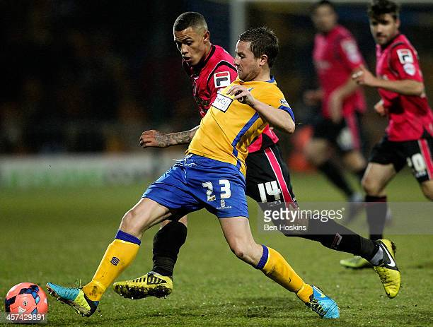 Jamie McGuire of Mansfield holds off pressure from Jonson ClarkeHarris of Oldham during the FA Cup Second Round Replay match between Mansfield Town...