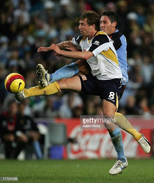 Jamie McMaster of the Mariners is challenged by Mark Milligan of Sydney FC during the round one ALeague match between Sydney FC and the Central Coast...