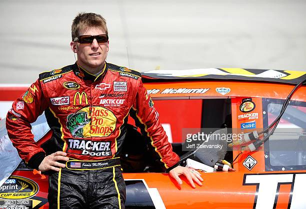 Jamie McMurray, driver of the Bass Pro Shops Chevrolet, stands next to his car on the grid during qualifying for the NASCAR Sprint Cup Series Autism...