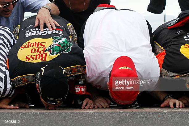 Jamie McMurray driver of the Bass Pro Shops/Tracker Boats Chevrolet celebrates by kissing the bricks with team coowner Chip Ganassi after winning the...