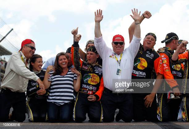 Jamie McMurray driver of the Bass Pro Shops/Tracker Boats Chevrolet celebrates by kissing the bricks with wife Christy McMurray coowner Felix Sabates...
