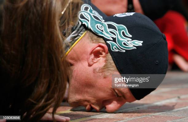 Jamie McMurray, driver of the Bass Pro Shops/Tracker Boats Chevrolet, and his team kiss the bricks after McMurray won the NASCAR Sprint Cup Series...