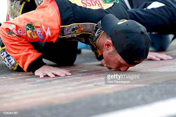 Jamie McMurray driver of the Bass Pro Shops/Tracker Boats Chevrolet and his team kiss the bricks after McMurray won the NASCAR Sprint Cup Series...