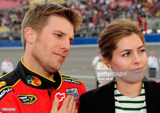 Jamie McMurray driver of the Bass Pro Shops/Tracker Boats Chevrolet and wife Christy look on from pit road prior to the start of the NASCAR Sprint...