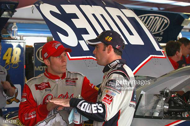 Jamie McMurray driver of the Ganassi Racing Dodge Intrepid R/T talks with fellow rookie Jimmie Johnson during practice for the EA Sports 500 at...