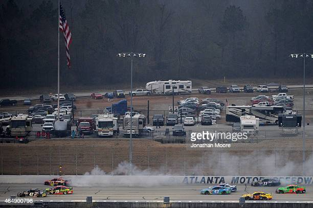 Jamie McMurray driver of the McDonald's Chevrolet and Denny Hamlin driver of the FedEx Ground Toyota are involved in a crash on the back stretch...