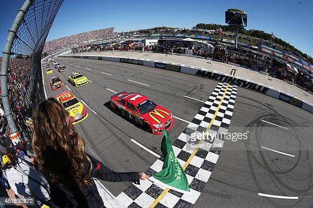 Jamie McMurray driver of the McDonald's Chevrolet and Joey Logano driver of the Shell Pennzoil Ford lead the field to the green flag for the running...