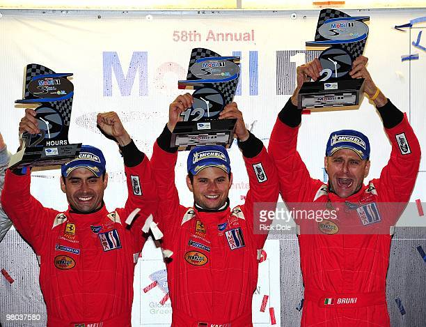 Jamie Melo Pierre Kaffer and Gianmaria Bruni celebrate on the podium after winning the GT2 class driving the Risi Competizione Ferrari 430 GT during...