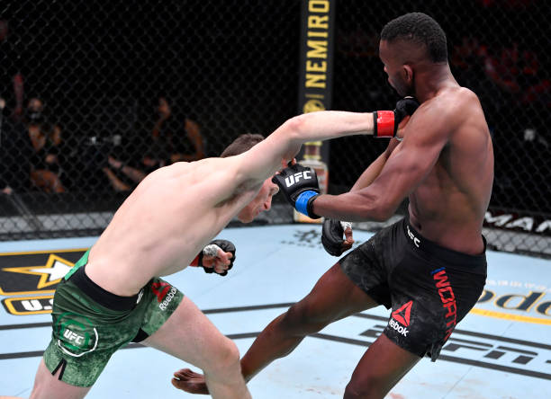 Jamie Mullarkey of Australia punches Khama Worthy in their lightweight fight during the UFC 260 event at UFC APEX on March 27, 2021 in Las Vegas,...