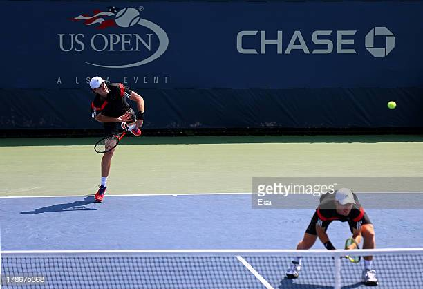 Jamie Murrary of Great Britain serves next to his partner John Peers of Australia during their men's doubles second round match against Feliciano...