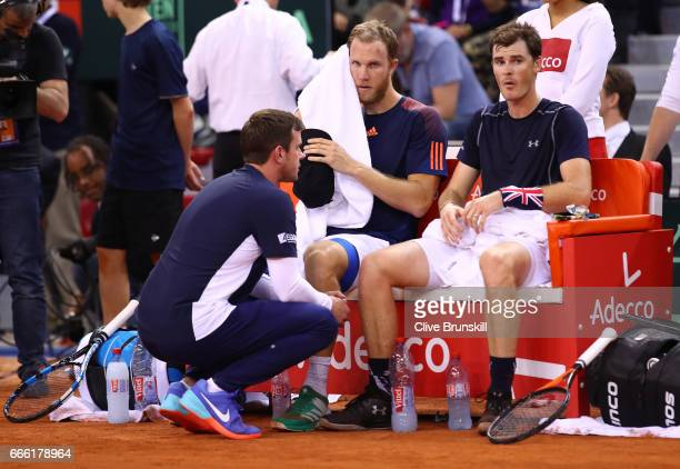 Jamie Murray and Dominic Inglot of Great Britain look dejected with captain Leon Smith after their doubles defeat to Julien Benneteau and Nicolas...
