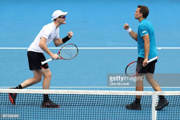 Jamie Murray of Great Britain and Bruno Soares of Brazil talk tactics in their second round men's doubles match against Leander Paes of India and...