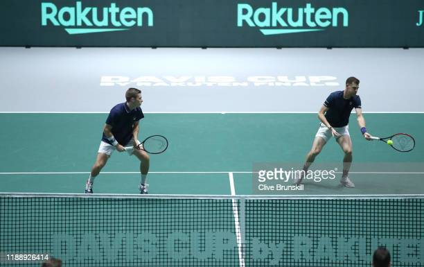 Jamie Murray of Great Britain plays a forehand shot as his playing partner Neal Skupski looks on during their Davis Cup Group Stage match against...