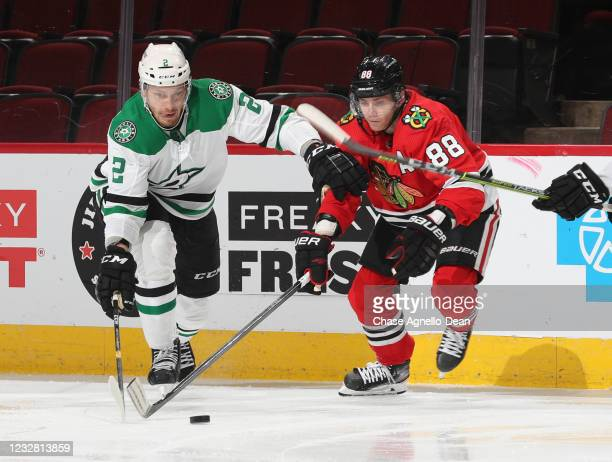 Jamie Oleksiak of the Dallas Stars and Patrick Kane of the Chicago Blackhawks battle for the puck during the second period at United Center on May...