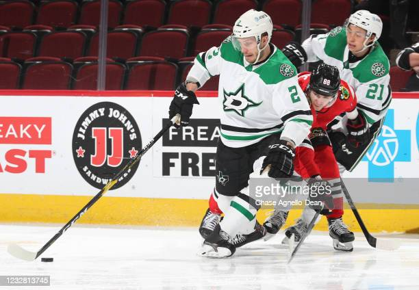 Jamie Oleksiak of the Dallas Stars controls the puck in front of Patrick Kane of the Chicago Blackhawks during the second period at United Center on...