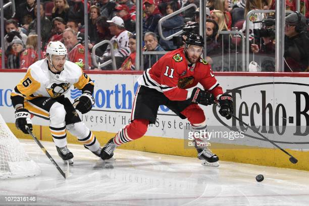 Jamie Oleksiak of the Pittsburgh Penguins and Brendan Perlini of the Chicago Blackhawks chase the puck in the third period at the United Center on...