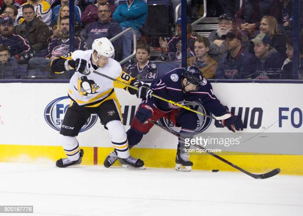 Jamie Oleksiak of the Pittsburgh Penguins and Matt Calvert of the Columbus Blue Jackets battle for the puck along the boards during third period of...