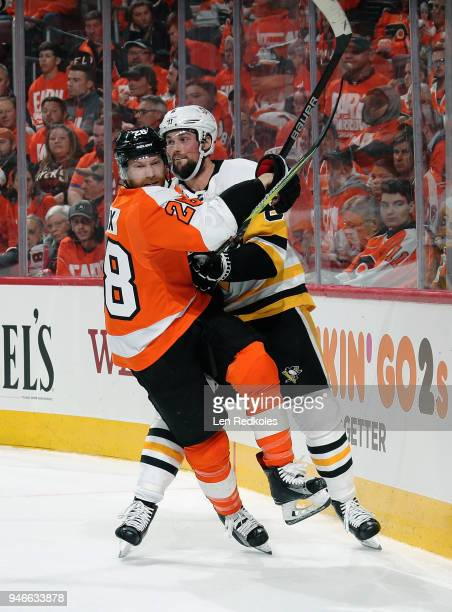 Jamie Oleksiak of the Pittsburgh Penguins checks Claude Giroux of the Philadelphia Flyers along the boards in Game Three of the Eastern Conference...