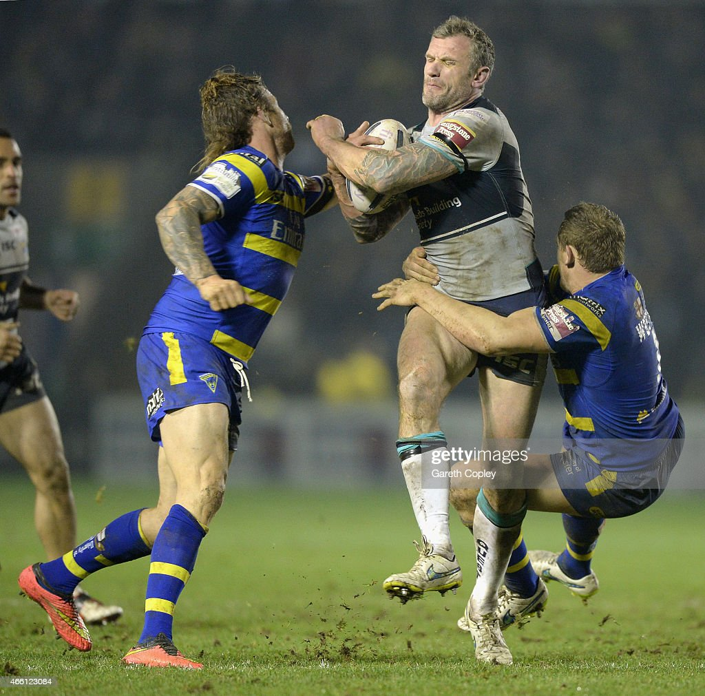 Jamie Peacock of Leeds Rhinos is tackled by Ashton Sims and Ben Harrison of Warrington Wolves during the First Utility Super League match between Warrington Wolves and Leeds Rhinos at The Halliwell Jones Stadium on March 13, 2015 in Warrington, England.