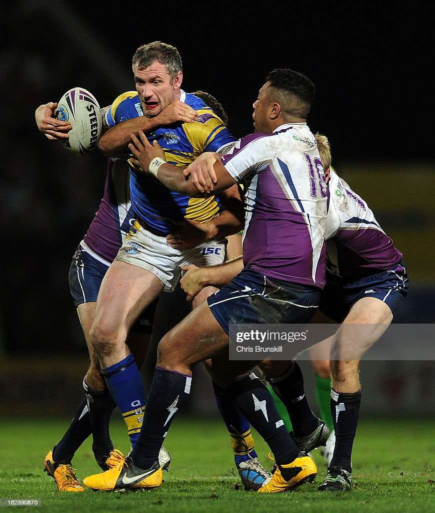 Jamie Peacock of Leeds Rhinos is tackled by Siosaia Vave of Melbourne Storm during the World Club Challenge match between Leeds Rhinos and Melbourne Storm at Headingley Carnegie Stadium on February 22, 2013 in Leeds, England.