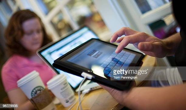Jamie Phelps syncs his newly purchased iPad while visiting a Starbucks Coffee with his wife Ann Phelps April 3 2010 in Fort Worth Texas Debuting...