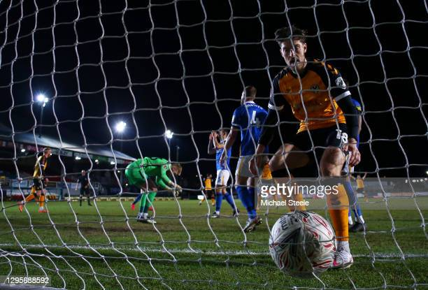 Jamie Proctor of Newport County collects the ball out the net as Adam Webster of Brighton and Hove Albion reacts after scoring an own goal for...