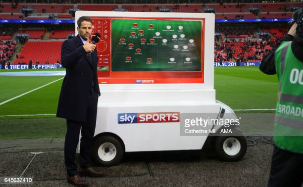 Jamie Redknapp reports pitch side for Sky Sports with a mobile screen with the teams on during the EFL Cup Final match between Manchester United and...