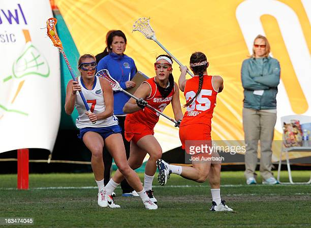 Jamie Reeg of the Florida Gators is defended by Kailah Kempney and Michelle Tumolo of the Syracuse Orange during the 2013 Orange Bowl Lacrosse...