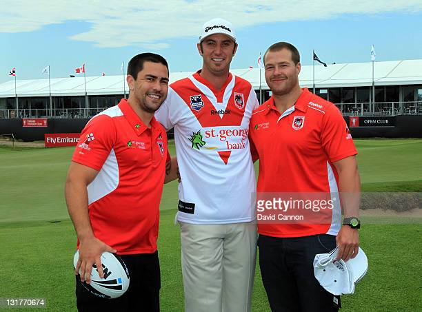 Jamie Soward and Trent Merrin of the St George Dragons present Dustin Johnson of the USA with one of the St George Dragons team jerseys during...