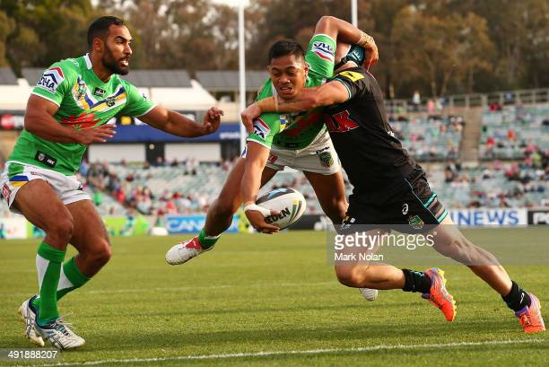 Jamie Soward of the Panthers attempts to tackle Anthony Milford of the Raiders before Milford scores a try during the round 10 NRL match between the...