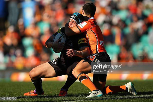 Jamie Soward of the Panthers is tackled by Luke Brooks of the Tigers during the round 17 NRL match between the Wests Tigers and the Penrith Panthers...