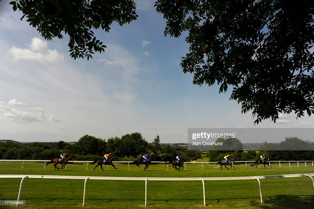 Jamie Spencer riding Cafe Society (L, orange) on their way to winning The Ashbrittle Stud Bibury Cup Stakes at Salisbury racecourse on June 26, 2013 in Salisbury, England.