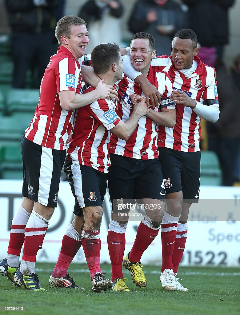 Jamie Taylor of Lincoln City (2nd left)celebrates with team mates Alan Pwer,Gary Mills and Adam Smith after scoring his sides second goal during the FA Cup with Budweiser Second Round match at Sincil Bank Stadium on December 1, 2012 in Lincoln, England.