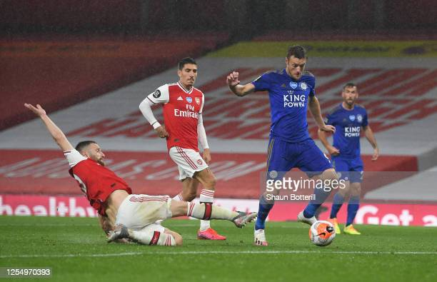Jamie Vardy of Leicester avoids the challenge of Shkodran Mustafi of Arsenal to score during the Premier League match between Arsenal FC and...