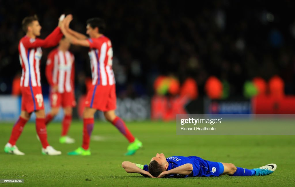 Jamie Vardy of Leicester City is dejected as the Atletico Madrid team cleberate after the UEFA Champions League Quarter Final second leg match between Leicester City and Club Atletico de Madrid at The King Power Stadium on April 18, 2017 in Leicester, United Kingdom.