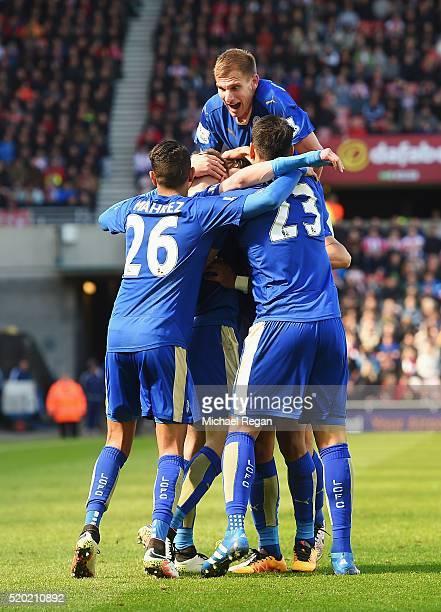 Jamie Vardy of Leicester City is mobbed by team mates in celebration as he scores their first goal during the Barclays Premier League match between...